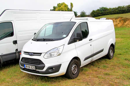 BUDAPEST, HUNGARY - JULY 27, 2014: White cargo van Ford Transit at the grass field.