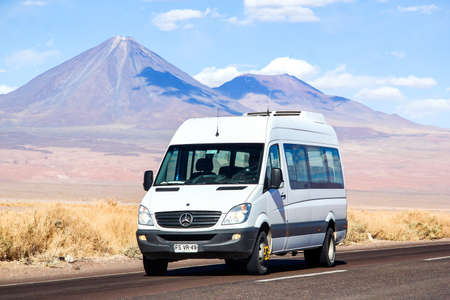 ANTOFAGASTA, CHILE - NOVEMBER 15, 2015: White minibus Mercedes-Benz Sprinter at the background of a volcano.