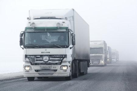 BASHKORTOSTAN, RUSSIA - FEBRUARY 7, 2016: Semi-trailer truck Mercedes-Benz Actros at the interurban freeway during a heavy fog.