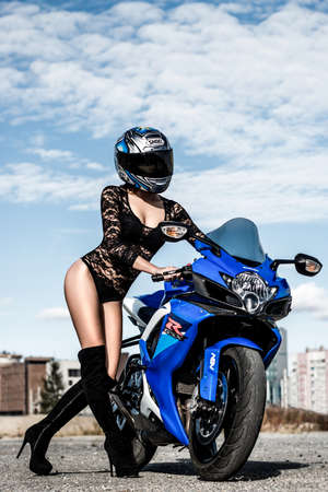 NOVYY URENGOY, RUSSIA - AUGUST 21, 2016: Sexy young woman in the Shoei helmet staying near the dark blue bike Suzuki GSX-R750.