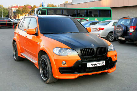Photo for Ufa, Russia - September 23, 2008: Black and orange SUV BMW (E70) X5 in the city street. - Royalty Free Image