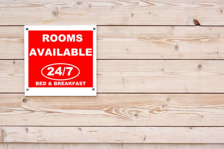 ROOMS AVAILABLE 24/7 BED & BREAKFAST Red White Sign on Timber Wall Background