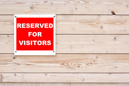 RESERVED FOR VISITORS Red White Sign on Timber Wall Background