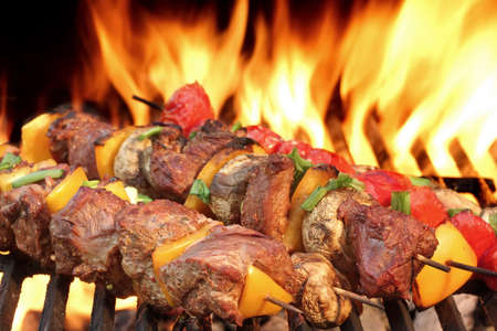 Barbecue Beef Kababs On The Hot Grill Close-up. Flames of Fire In The Background