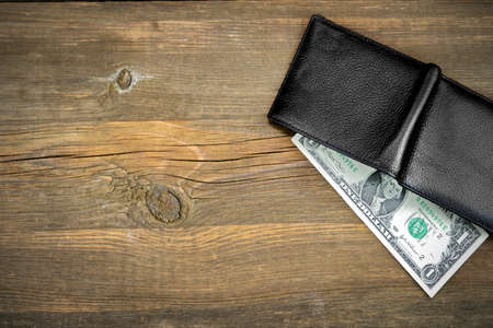 Open Male Black Leather Wallet With USA One Dollar Bill On Old Rough Brown Wood Background With Copy Space