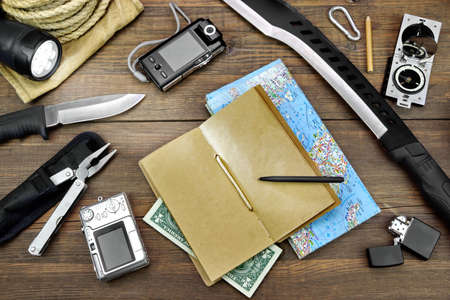 Photo pour Survival Kit Laid Out On The Rustic Rough Wood Floor. Items Include,  Blank Notebook, Money, Pen, Flashlight, Knife, Machete, Rope, Bag, Tools - image libre de droit