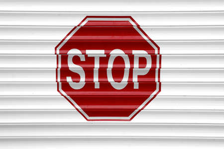 Red Stop Sign On The Automatic  Aluminum Roll-up White Garage Gate