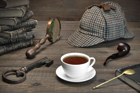 Photo pour Sherlock Holmes Concept. Private Detective Tools On The Wood Table Background. Deerstalker Cap,  Magnifier, Key, Cup, Notebook, Smoking Pipe. - image libre de droit
