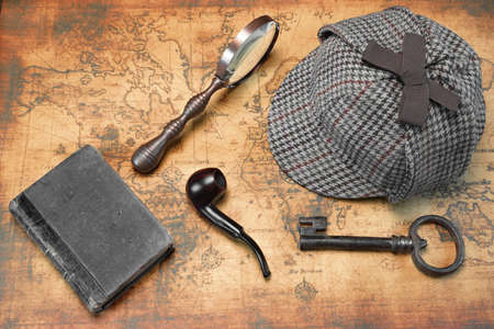 Photo pour Overhead View Of Sherlock Holmes Deerstalker Hat  And Private Detective Tools On The Old World Map Background. Items Include Vintage Magnifying Glass, Retro Key, Hand Book Or Notepad, Smoking Pipe - image libre de droit