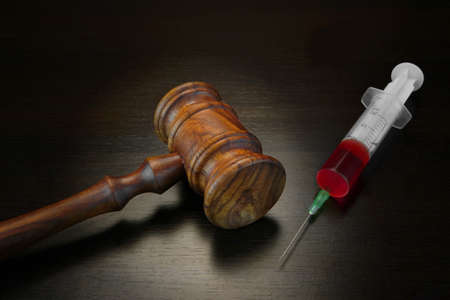 Judges Gavel And Medical Injection Syringe With Red Liquid On The Black Wood Background, Close-up, Top View