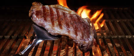 Photo pour Grilled Beefsteak From Marbled Black Angus Meat On Hot Barbecue Charcoal Grill, Closeup View. Juicy BBQ Pepper Beef Steak On Spatula And Flaming Grill In Background. Grill Party Or Cookout Concept. - image libre de droit