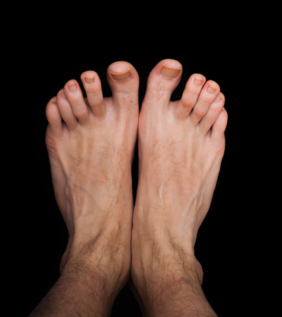Pair of caucasian male feet isolated towards black