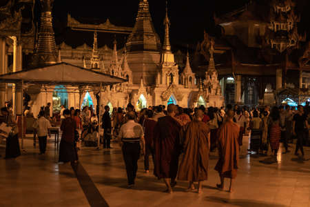 Photo pour Yangon, Myanmar - December 30, 2019: Three monks and visitors walks around the Shwedagon Pagoda and its surrounding golden structures at night - image libre de droit