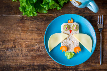 Breakfast for kids: funny healthy sandwich on plate and copy space