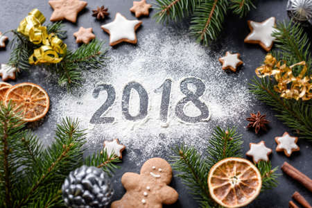 Photo pour Happy New Year 2018 greeting written on flour. Gingerbread cookies, spices, fir tree and Christmas toys around. Christmas, New Year winter holidays greeting card. - image libre de droit