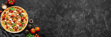 Photo pour Italian pizza and pizza cooking ingredients on black concrete background. Tomatoes on vine, mozzarella, black olives, herbs and spices. Copy space for text. Banner composition - image libre de droit