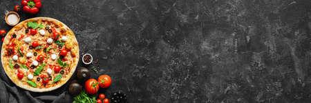 Foto de Italian pizza and pizza cooking ingredients on black concrete background. Tomatoes on vine, mozzarella, black olives, herbs and spices. Copy space for text. Banner composition - Imagen libre de derechos