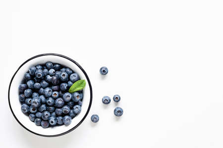 Organic blueberries in bowl on white background. Table top view. Copy space for text