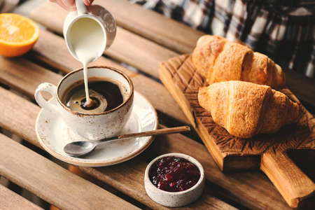 Photo pour Pouring cream into cup of black coffee. Tasty breakfast table set with croissants, jam and coffee - image libre de droit