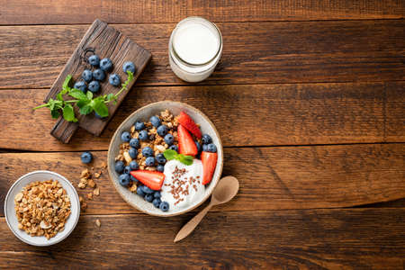Photo for Oat granola with greek yogurt and summer berries in a bowl. Top view on a rustic wooden table background, copy space. Nutrition, healthy eating concept - Royalty Free Image