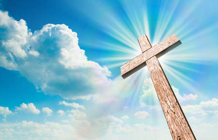 Wood cross on blue sky. Christian background.