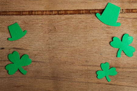 Happy St Patricks Day tag with corner border of shiny shamrocks over a rustic wood background. Place for text