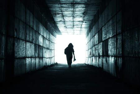 silhouette of a person reaching the light at the end of the tunnel