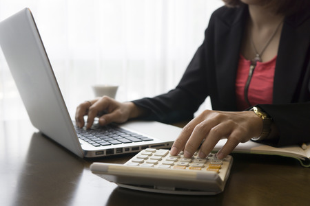 Finance & Business, women Analysis Business Accounting,hands typing keyboard and pressing calculator buttons over documents,financial manager taking notes  in office,selective focus,vintage tone