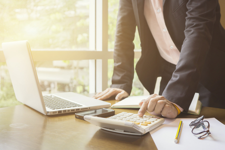 calculate,finance,accounting,Businessman analyzing investment charts with calculator .Accounting with technology,man using laptop at office Analyze plans.selective focus,vintage color