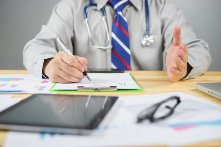 Doctor working in hospital with Stethoscope,Describe the symptoms to the patient listener, Healthcare medical concept,clipboard and Laptop on desk.hand of specialist on a prescription,selective focus
