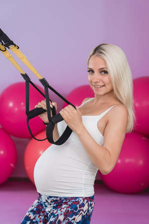 Young pregnant attractive woman training with trx fitness straps in the gyms studio