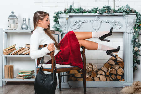 Foto de gorgeous young female in a red skirt and white pullover sitting in retro armchair on a christmas decorated wall background. Erotic legs in white socks and black varnish high heells - Imagen libre de derechos