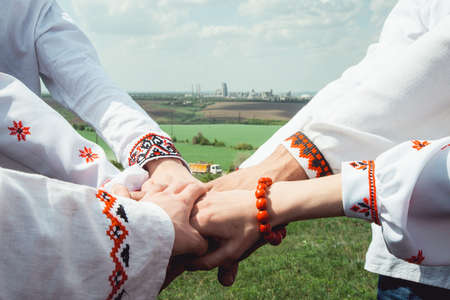 people are dressed in traditional Ukrainian clothes holding their hands together, success unification of the nation concept