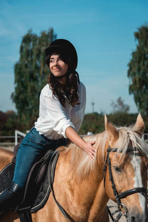 Photo for Portrait of young brunette woman in a white shirt and helmet on a horse. learns to ride a horse. riding lessons on a horse epodrom - Royalty Free Image
