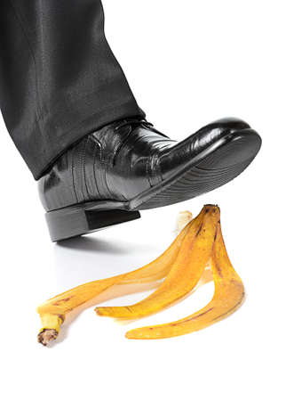 Businessman foot about to slip and fall on a banana peel on white background