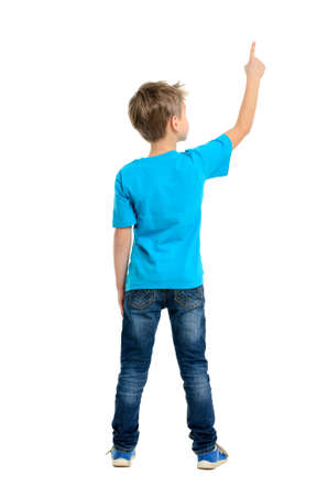 Rear view of a school boy over white background pointing upwards  Full length portrait