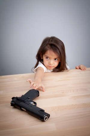 Foto de parents not keep gun in safe place, children can have gun for accident. safety concept - Imagen libre de derechos