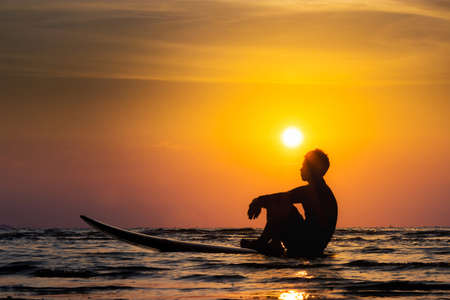Photo pour Silhouette of surf man sit on a surfboard. Surfing at sunset beach. Outdoor water sport adventure lifestyle.Summer activity. Handsome Asia male model in his 20s. - image libre de droit