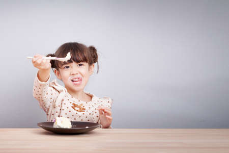 Photo pour Kids enjoy eating concept : Happy little cute mixed race girl enjoy eating cake with smiley face , tongue stick with spoon in her hand for invite to eat. Kid poster background. - image libre de droit