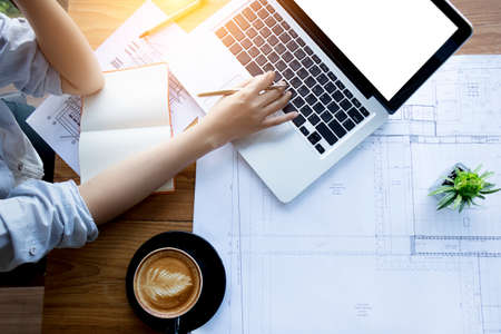 Foto de architect , engineering , creative and designer workspace concept : Top view of Asian female architect working with blueprint , notebook and laptop on architectural project , anonymous face. - Imagen libre de derechos