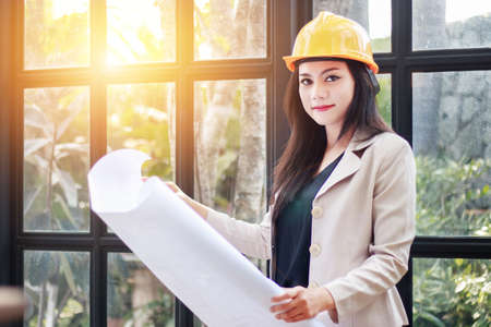 Photo pour portrait of beautiful Asian woman architect builder with yellow helmet hard hat studying blueprint plan of the rooms, serious civil engineer working with documents on construction site - image libre de droit