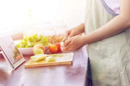 Foto de Asian woman prepare ingredients for cooking follow cooking online video clip on website via tablet. cooking content on internet technology for modern lifestyle concept - Imagen libre de derechos