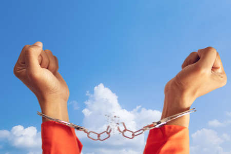 Foto de freedom concept. two hands of prisoner with broken handcuff for freedom meaning with blue sky at background - Imagen libre de derechos