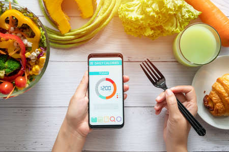 Photo for Calories counting , diet , food control and weight loss concept. woman using Calorie counter application on her smartphone at dining table with salad, fruit juice, bread and vegetable - Royalty Free Image