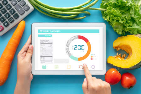 Photo for Calories counting , diet , food control and weight loss concept. woman using Calorie counter application on tablet at dining table with fresh vegetable and calculator - Royalty Free Image