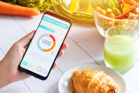 Photo for Calories counting and food control concept. woman using Calorie counter application on her smartphone with salad , vegetable, juice and croissant on dining table - Royalty Free Image