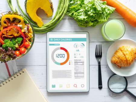 Photo for Calories counting , diet , food control and weight loss concept. tablet with Calorie counter application on screen at dining table with salad, fruit juice, bread and vegetable - Royalty Free Image