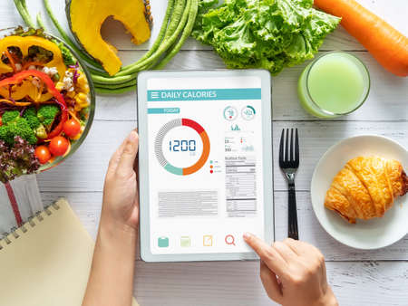 Photo pour Calories counting , diet , food control and weight loss concept. woman using Calorie counter application on tablet at dining table with fresh vegetable salad - image libre de droit