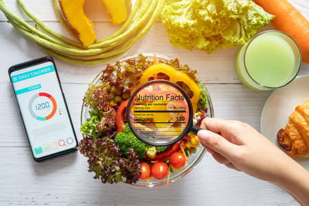 Foto de nutritional information concept. hand use the magnifying glass to zoom in to see the details of the nutrition facts from food , salad bowl - Imagen libre de derechos
