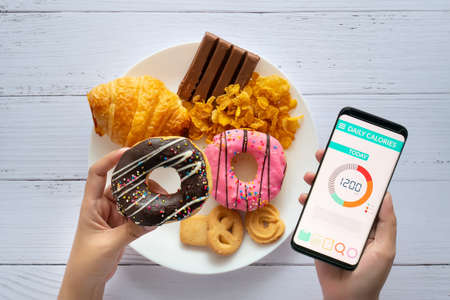 Photo for Calories counting and food control concept. woman using Calorie counter application on her smartphone with doughnut in hand and snack , cookies on plate at background - Royalty Free Image